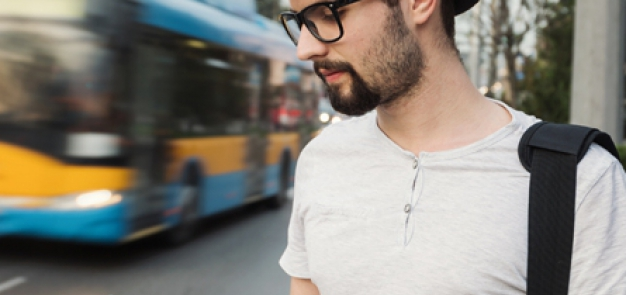 Man looking down at phone with bus in the background